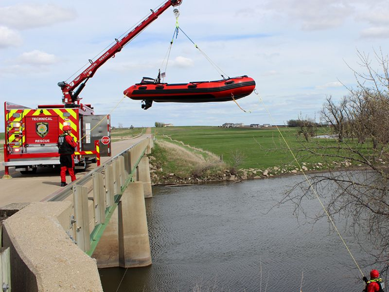 M301 Miami Twp Rescue Truck with Scene Commander uses crane to lower the boat from a bridge deck